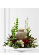 a funeral wreathe around an urn red flowers white flowers